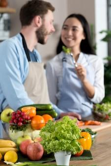 ぼやけているフォーカスカップル立っているキッチンカウンターの後ろに健康的なサラダを供給