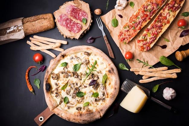 Повышенный вид свежей вкусной итальянской кухни с ингредиентами на черной поверхности