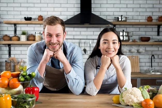 エプロンを着て彼らのモダンなキッチンでカメラを見て幸せなカップルの肖像画