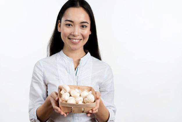 アジアの女性の白い背景に対してキノコ容器を保持