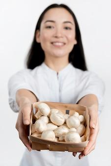白い背景で生のきのこコンテナーを示す焦点がぼけた女性