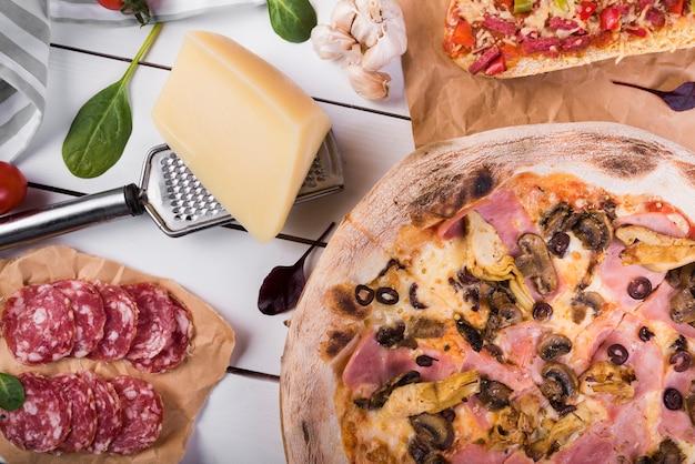 キノコのペパロニピザとチーズブロックのクローズアップ。おろし金と食材