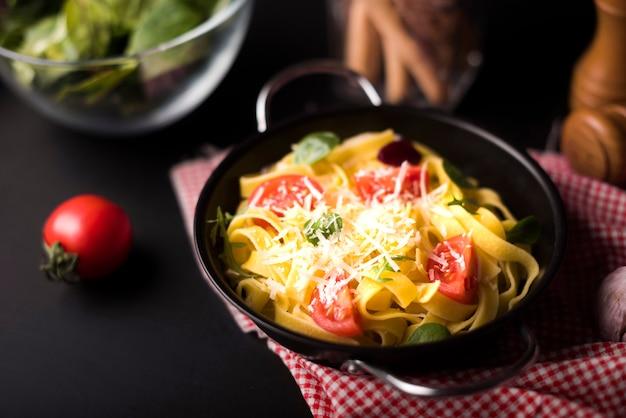 チェリートマトのスライスを持つコンテナーで安っぽい健康的なタリアテッレパスタのクローズアップ