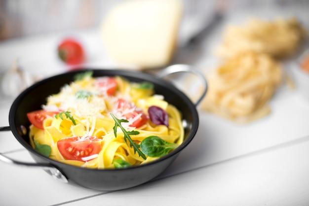 新鮮な食材とチーズのおいしいタリアテッレのクローズアップ