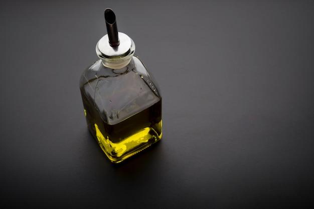 暗い背景にオリーブオイルの瓶