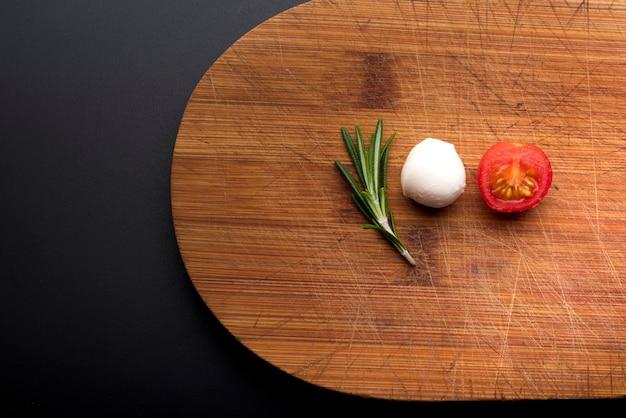 フレッシュチーズのクローズアップ。まな板の上のローズマリーと半分のトマト