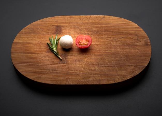 トマト;ローズマリーと黒の背景上の木製のまな板の上のチーズ
