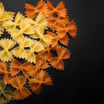 黒の背景にカラフルなイタリアの蝶ネクタイ新鮮なパスタ
