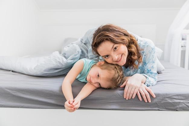 幸せな母と娘がベッドに横になっています。