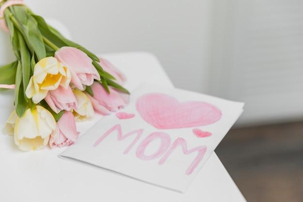 チューリップの花の束とお祝いグリーティングカードのクローズアップ