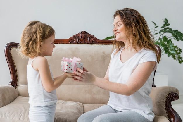 彼女の小さな娘から母の日ギフトを受け取って幸せな母
