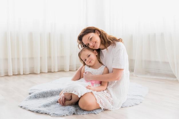 ふわふわのカーペットの上に座っている彼女の子供の女の子を持つ母の正面図