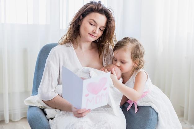 Маленькая девочка целует ребенка в лоб, пока мать читает открытку, сидя на кресле у себя дома