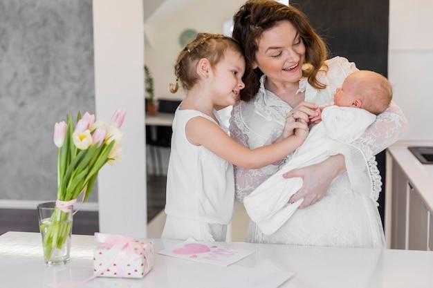 Счастливая мать с двумя милыми детьми стоит возле белого стола