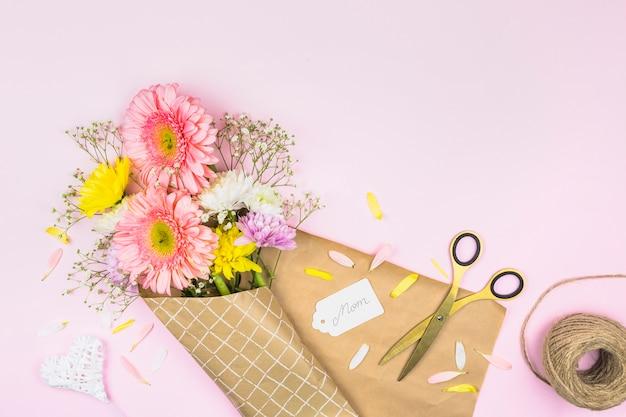 ママの単語とはさみのタグの近くのラップで新鮮な花の花束