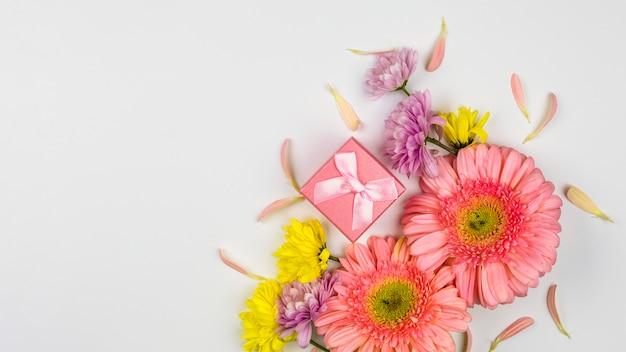 Букет свежих цветов возле подарочной коробки и лепестков
