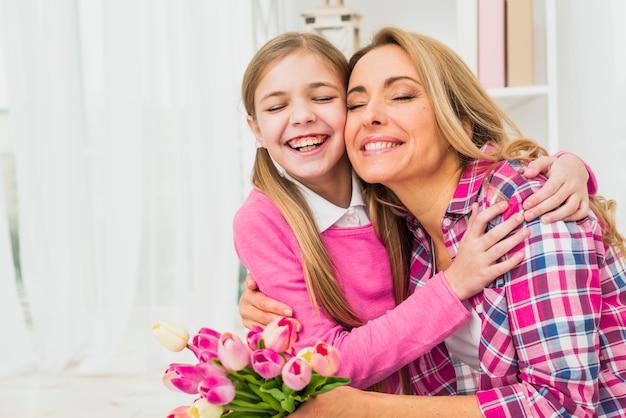 Мать с тюльпанами обнимает дочь