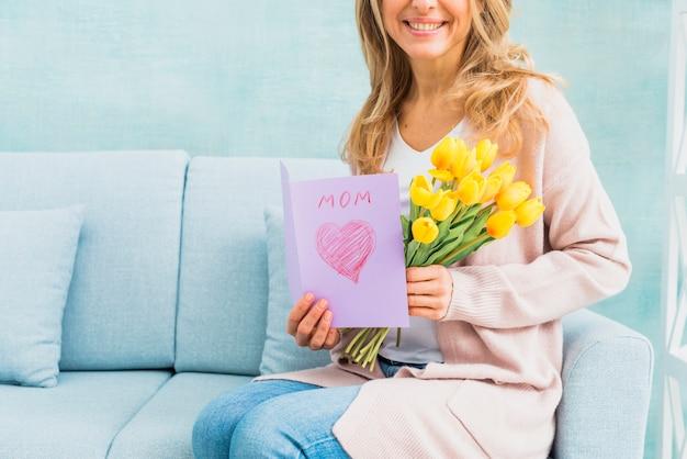 Девушка улыбается с тюльпанами и открыткой для мамы