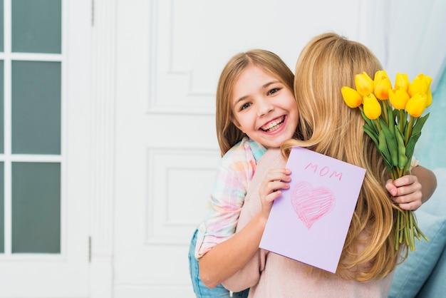 Дочь с подарками улыбается и обнимает маму