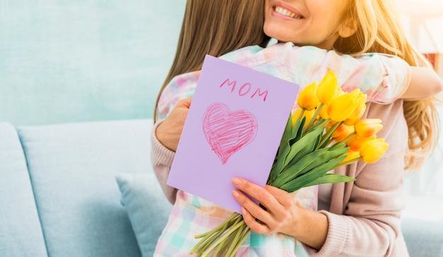 Мать с подарками обнимает дочь и улыбается