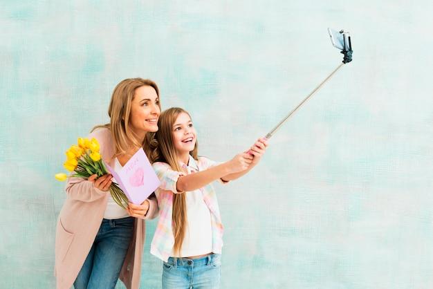 Дочь и мать, улыбаясь и принимая селфи