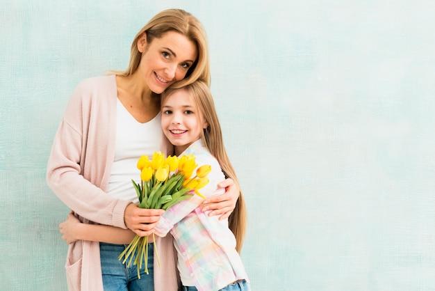 Мать и дочь с тюльпанами обнимаются и улыбаются
