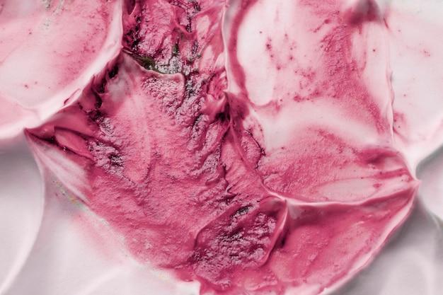 ピンク色のペンキが柔らかい質感のクリーミーな泡の背景と混合