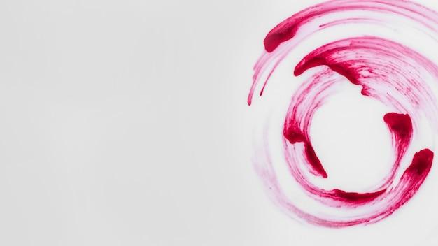 白い背景の上の渦巻き模様のデザインを作る赤い色のブラシストローク