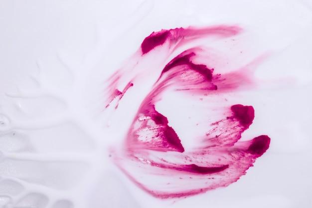 Ярко-розовые рисованные акварельные мазки на гладких белых обоях