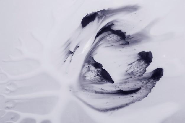 白い泡の背景の上の装飾的な黒い色のブラシストローク