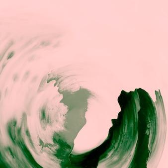 桃の背景の上の緑色のペイントブラシストローク