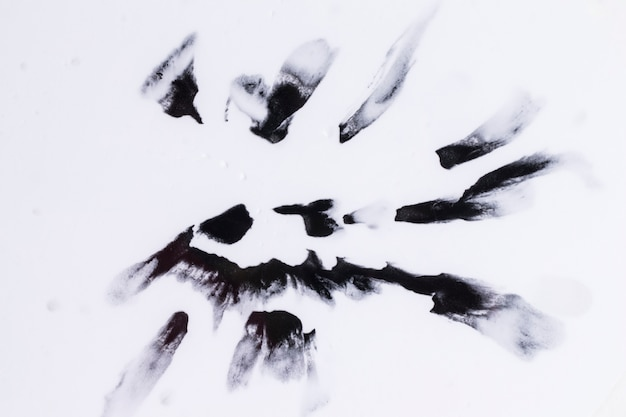 Черные акварельные капли, изолированные на гладкой белой поверхности