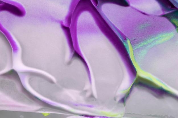 紫と黄色の色の塗料が白い織り目加工のキャンバスに染み