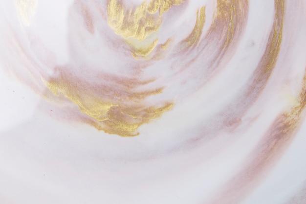 黄金と茶色のペンキの塊と装飾的な織り目加工の白い泡の背景