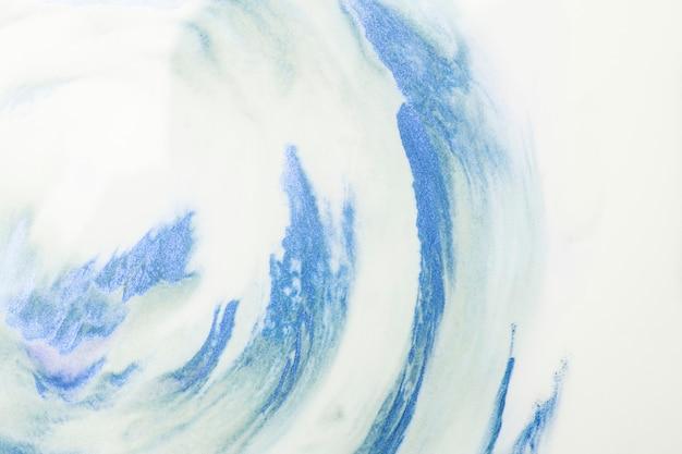 白い泡の背景の上の青い水彩画ストロークのクローズアップ