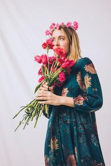Привлекательная чувственная женщина с венком на голове пахнет букетом цветов