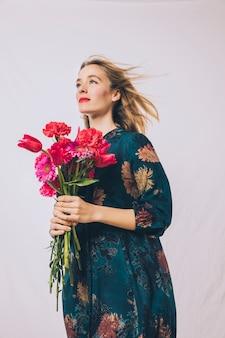 花の花束を持つ魅力的な肯定的な官能的な女