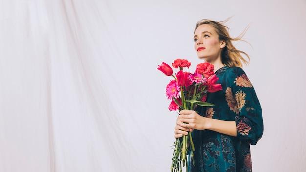 花の花束を持つ魅力的な肯定的な女性