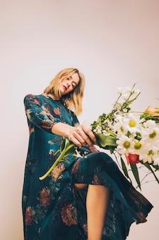 新鮮な花の花束とドレスの魅力的なゴージャスな女性