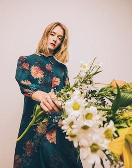 Привлекательная шикарная женщина в платье держит букет свежих цветов