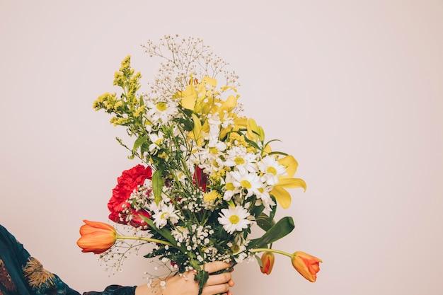 新鮮な芳香の花の束を保持している女性