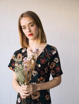 乾燥植物の花束と官能的な悲しい女