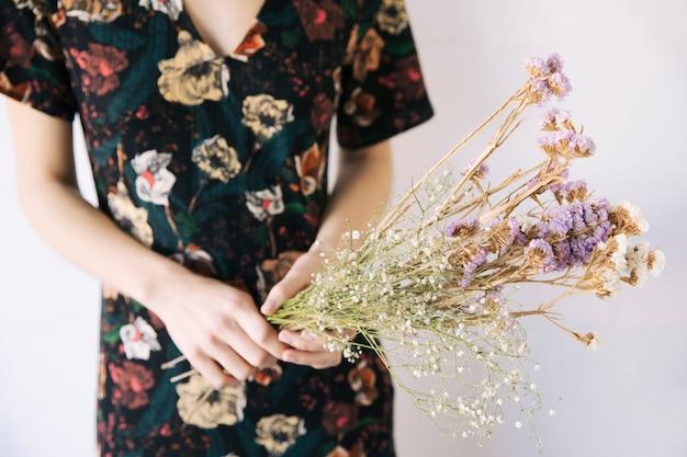 乾燥植物の花束を保持している女性