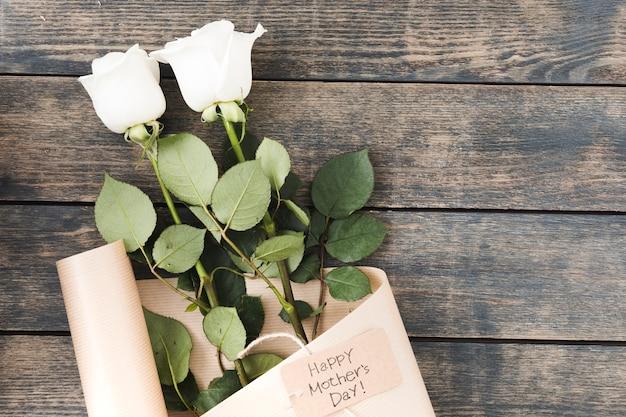 テーブルの上のバラと幸せな母の日碑文