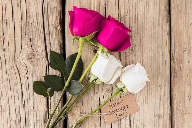 木製のテーブルにバラと幸せな母の日碑文