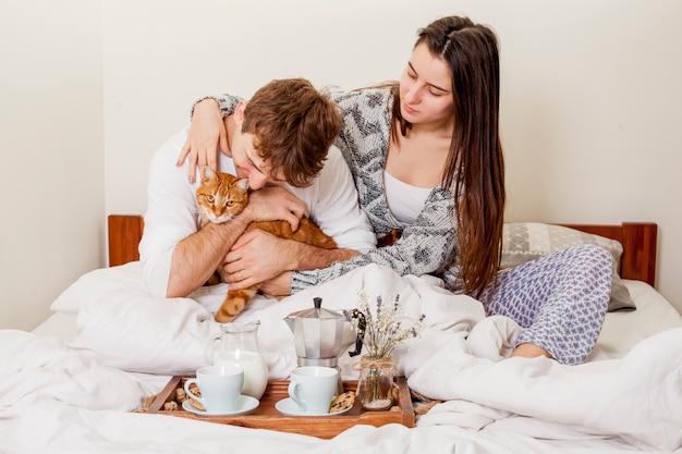 ベッドで朝食を持っている若いカップル