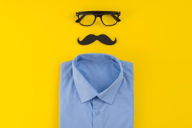 口ひげとテーブルの上のシャツとメガネ