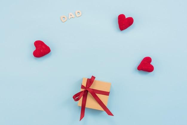 Надпись папы с подарочной коробкой и красными игрушечными сердечками