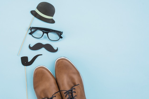 メガネと紙の口ひげを持つ男の靴