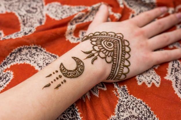 Рука женщины с красивыми красками менди